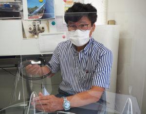 フェイスシールドを製作した鈴木機械彫刻所の鈴木伴彦社長。フェイスシールドはオーダーメイドで対応、サイズや角度調整、暑さ対策といった様々な工夫も施(ほどこ)す。自社製のアクリル製のパーテーションボードを前に