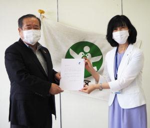 「(マスクを寄贈してくれた)一人ひとりに感謝したい」と感謝状を熊井理事長(左)に贈呈する栗田区長