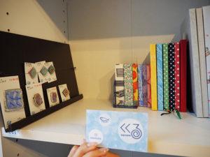 今回初出展となる横浜のハンドメイドグループ「くくる」(リンクはインスタグラム)では、手製本と紙物文具を扱っている。左側に展示されたブローチの外側の素材はレジン(合成樹脂)だが、中は紙でできているという