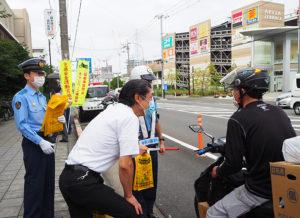 太刀野署長(左)や港北安全運転管理者会の安齊博仁会長(中央)もバイクや自転車を運転する通行人に安全運転の呼び掛けを行っていた