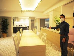 野村不動産のエリアマネジメント部長・泉山秀明さんが「まちのリビング」をナビゲート。シェアダイニングの奥にはシェアキッチンがある