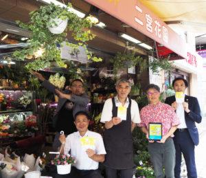 日吉サンロード商店会会長の二宮陸次(よしつぐ)さん(中央)を囲んで。中央通りの「二宮花園」店舗ではラジオ体操カードを配布している