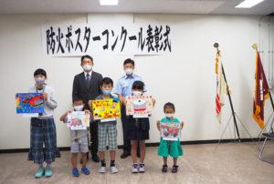 横浜市港北消防署と港北火災予防協会が初企画・開催した「防火ポスターコンクール」の表彰式で。後列中央が吉山会長、右が吉田署長