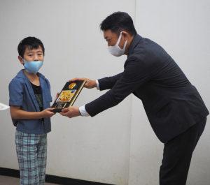 最優秀賞の記念品として吉山会長から手渡された記念の表彰楯(たて)にはポスターのデザインも
