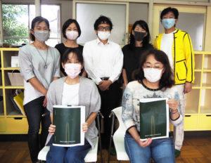「70周年記念誌」編集委員の皆さん。最終稿を手にする委員長の榊原さん(右手前)、横浜綜合写真の稲田さん(後列中央)、猿渡会長と