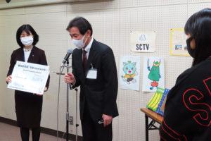 土屋校長が橋渡しを行い、学校を代表して図書委員長の安達さんにメッセージボードが手渡された