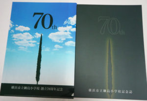 「綱島小学校創立70周年記念誌」(右)も無事完成し生徒や参加者に配布された。特注のクリアケース(左)も美しいイトスギの姿で、手に取った人の感動を誘う