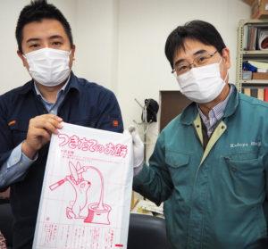 「つきたてのお餅」のパッケージを手にする飯山洋平社長(左)、飯山貴志常務。昭和時代を過ごした世代からは「懐かしい」との声も多数届くという
