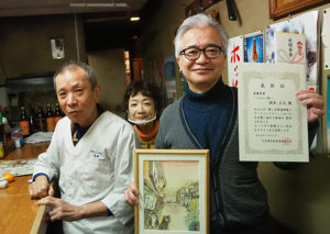 作品の舞台となった焼き鳥店「鳥雄(とりゆう)」にて、受賞者の潤米(うるめ)さん(右)。店主の小林さん夫妻と