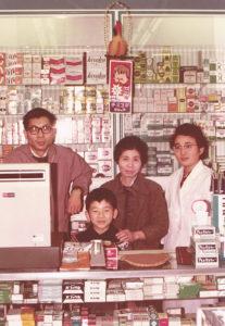 小学生時代の相沢淳さん。父で3代目の善雄(ぜんお)さん、祖母で2代目の芳(よし)さん、母で管理薬剤師の康子さん(右)と(日吉堂薬局提供)