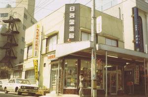 現在地で建てられた「二代目」の建物となる、1971年頃の「日吉堂薬局」。日吉中央通りから普通部通り方面に店舗建物の敷地があった(日吉堂薬局提供)