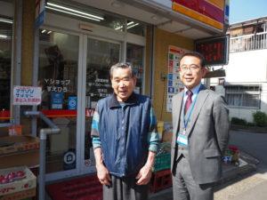 """荒金さん(左)と丹波校長。荒金さんは1966(昭和41)年7月にこの地で創業して以来54年間事業を行ってきた。「周囲のお店が閉店して残念。""""地域""""のお店として商売を続けなければ」との使命感で経営を行っているという"""