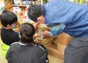 「量り売り」を行う玄米を入れた樽に、児童らが制作した「手作りPOP」が飾られた
