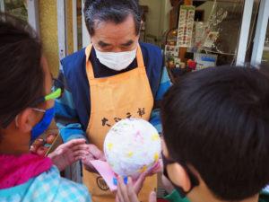 大曽根小学校周辺の交番、商店街や郵便局、見守り活動を行う人々などへの感謝の想いを込めて、灯籠をプレゼントするという試みが行われた(3月24日、農家産直米すえひろ大曽根店)