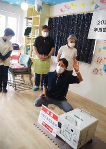 発電機を選定した同デイサービス指導員で事務担当の松永泰さんがその理由を説明していた