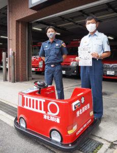 港北消防署前で、今年はなかなか開催できないイベント時に登場する「ミニ消防車」と。予防係の千葉係長(右)