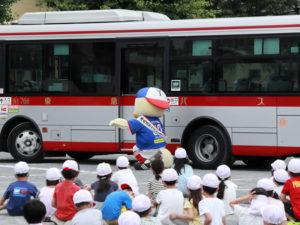 大きなバスの「後輪」に要注意。バスに轢(ひ)かれそうになる横浜F・マリノスのマスコットキャラクターで港北区安全安心大使を務める「マリノスケ」(駒林小学校)