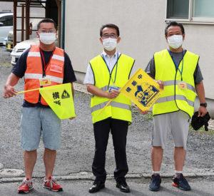 マリノスケとミズキーの「交通安全」旗を手に持ち、鮮やかな「黄色いベスト」をまとう荒巻さん、丹波校長、齋藤さん(右より)
